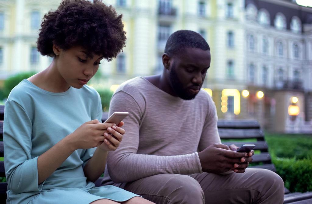 Girlfriend and boyfriend chatting in their smartphones, sitting on bench, ignore